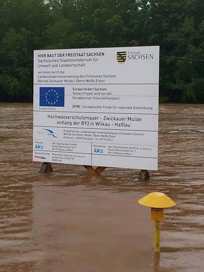 Hinweisschild mitten in den dreckig-braunen Fluten: Hier baut der Freistaat Sachsen eine Hochwasserschutzmauer Zwickauer Mulde entlang der B93 in Wilkau - Haßlau