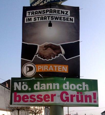 Zwei übereinander hängende Wahlplakate. -- Oben die Piratenpartei 'Transparenz im Staatswesen'. -- Unten die Grünen 'Nö, dann doch besser Grün!'.