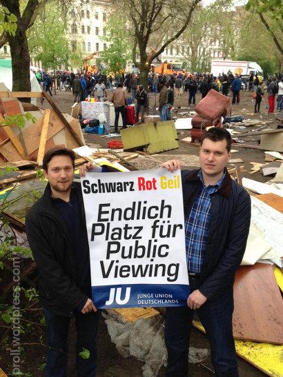 Zwei Mitglieder der Jungen Union mit einem Plakat am geräumten Flüchtlingscamp Oranienplatz (Berlin), auf dem Plakat steht: 'Schwarz Rot Geil: Endlich Platz für Public Viewing - Junge Union Deutschlands'