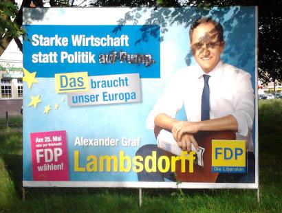 Ein Wahlplakat der FDP mit dem Claim: 'Starke Wirtschaft statt Politik auf Pump -- Das braucht unser Europa', bei dem jemand die Worte 'auf Pump' übersprüht hat, so dass nur noch 'Starke Wirtschaft statt Politik' stehen bleibt
