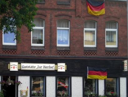 Eine Kneipe in Hannover mit dem Namen 'Zur Bierfee'; Kneipe und Wohnung darüber behangen mit Flaggen der Bundesrepublik Deutschland.