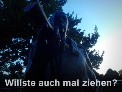 Denkmal, das eine riesengroße Rolle in der Hand hält und auf den Betrachter zustreckt. Darunter der Text: 'Willste auch mal ziehen?'