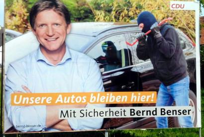 Plakat der CDU im brandenburger Landtagswahlkampf. Im Vordergrund Kandidat Bernd Benser, hinter ihm ein maskierter Mann, der sich mit einem Brecheisen an einem Auto zu schaffen macht. Dazu der Text: 'Unsere Autos bleiben hier! Mit Sicherheit Bernd Benser. CDU'