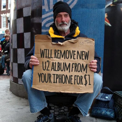 Bettler mit einem Schild: 'Will remove new U2 album from your iPhone for $1'