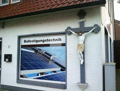 Werbung 'Befestigungstechnik', daneben ein obszön großes Kruzifix...