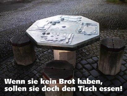 Foto eines Tisches, der zu einem künstlerisch ausgestalteten Brunnen vor der Neustädter Kirche in Hannover gehört. In die metallische Platte des Tisches sind verschiedene Speisen eingeprägt. Spruch dazu: 'Wenn sie kein Brot haben, sollen sie den Tisch essen!'