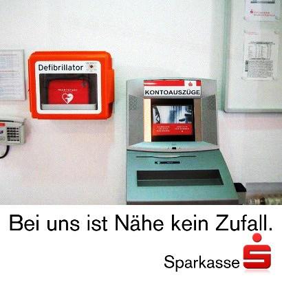 Bild aus einer Sparkasse. Neben dem Kontoauszugdrucker hängt ein Defibrillator an der Wand. Dazu der Text: 'Bei uns ist Nähe kein Zufall. Sparkasse'