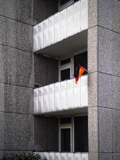 Eine BRD-Flagge an einem Balkon an trister Beton-Architektur