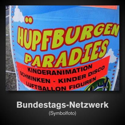 Am Straßenrand aufgehängtes Plakat: Hüpfburgen Paradies... Kinderanimation... Schminken... Kinder Disco... Luftballon Figuren... -- darunter der Text 'Bundestags-Netzwerk (Symbolfoto)'.