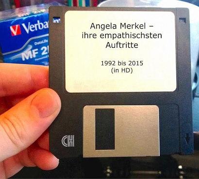 Hand, die eine Diskette hält. Auf der Diskette ein Label mit dem Text 'Angela Merkel -- ihre empathischten Auftritte. 1992 bis 2015 (in HD).
