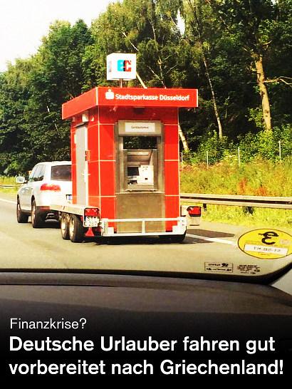 Foto eines Autos, auf dessen Anhänger ein Geldautomat der Düsseldorfer Sparkasse steht. Dazu der Text: Finanzkrise? Deutsche Urlauber fahren gut vorbereitet nach Griechenland!
