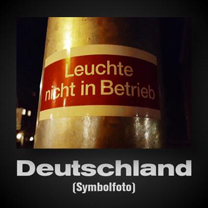 Hinweisaufkleber an einem Laternenmast: 'Leuchte nicht in Betrieb'. Darunter der Text: 'Deutschland (Symbolfoto)'.