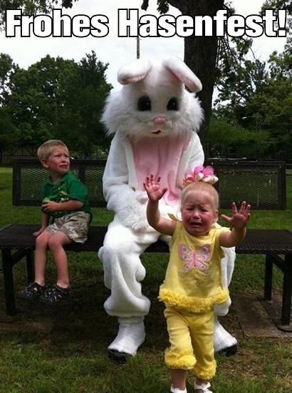 Foto eines Menschen im infantil-kitschigem Hasenkostum, der auf einer Bank sitzt. Dazu zwei Kinder. Eines sitzt ebenfalls auf der Bank und schaut mit angstvollem Blick zum Hasen, ein anderes läuft in großer Angst davon. Darüber der Text: 'Frohes Hasenfest!'