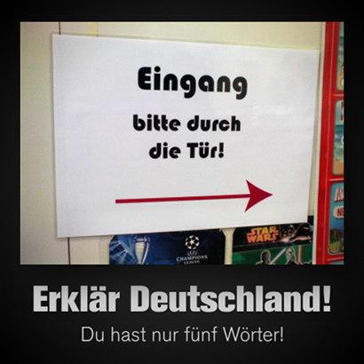 Hinweisschild: 'Eingang bitte durch die Tür'. Dazu der Text: 'Erklär Deutschland! Du hast nur fünf Wörter!'.