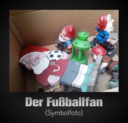 Foto eines Kartons, in dem eine hässliche grüne Lampe und einige Gartenzwerge liegen. Einer der Gartenzwerge trägt ein Trikot von Hannover 96 (mit TUI-Reklame) und einen Fußball. Dazu der Text: 'Der Fußballfan (Symbolfoto)'.