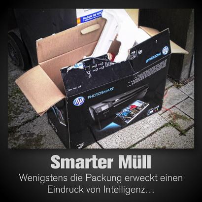 Photo eines Pappkartons einer Druckerverpackung, der an einer Mülltonne abgestellt ist. Aufdruck 'Photosmart'. Dazu der Text: 'Smarter Müll. Wenigstens die Packung erweckt einen Eindruck von Intelligenz'.