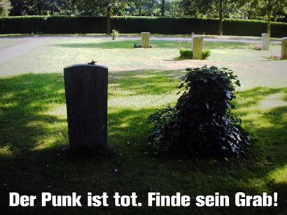 Szene auf einem Friedhof. Von hinten sind mehrere Grabsteine zu sehen. Einer der Grabsteine, vorne im Bild, ist mit Efeu überwuchert. Darunter der Text: 'Der Punk ist tot. Finde sein Grab!'.