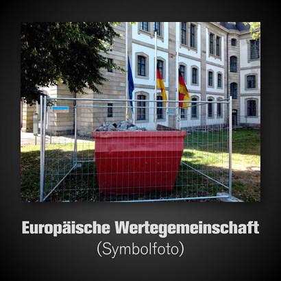 Foto eines mit Bauzaun abgesperrten Müllcontainers voller Bauschutt vor einem repräsentativen Verwaltungsgebäude in Hannover. Davor drei Flaggen auf Halbmast: Die Flagge der EU, die Flagge der BRD, die Flagge Niedersachsens. Dazu der Text: 'Europäische Wertegemeinschaft (Symbolfoto)'.