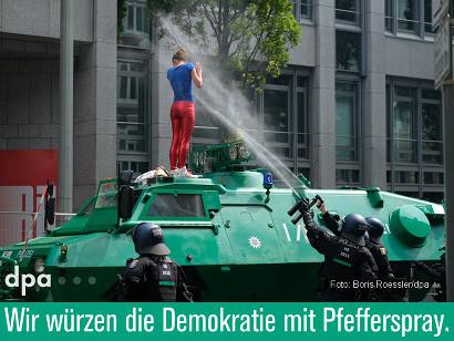 Ein Teilnehmer der laufenden G20-Proteste steht auf einem Polizeipanzer und wird von unten von zwei Polizisten mit Pfefferspray besprüht