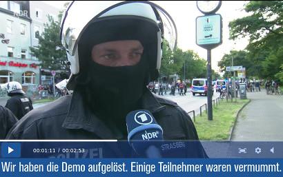 Screenshot aus der Berichterstattung des NDR zu den Protesten gegen den laufenden G20 in Hamburg. Es wird ein Polizeibeamter interviewt, der das Interview in Sturmmaske gibt. Darunter mein Text: Wir haben die Demo aufgelöst. Einige Teilnehmer waren vermummt.