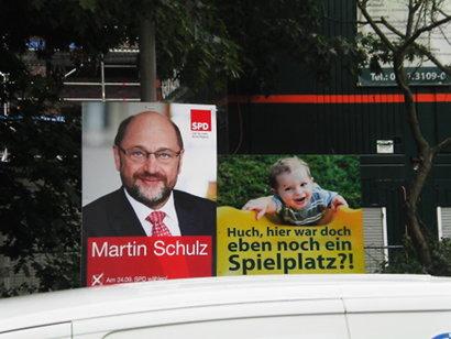 Nebeneinander zweier Plakate: SPD-Personenwahlplakat Martin Schulz und 'Huch, hier war doch eben noch ein Spielplatz'.