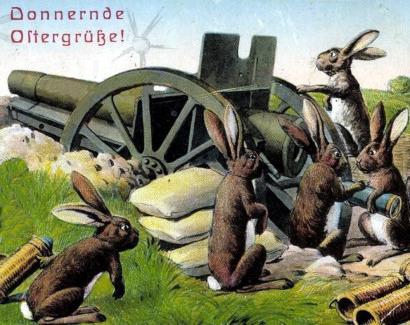 Alte Postkarte. Osterhasen stehen an einem großen Geschütz. Dazu der Text: Donnernde Ostergrüße