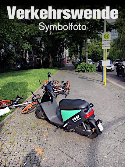 Foto eines asozial und platzfressend quer auf dem Fußweg abgestellten Motorrollers, vor dem Motorroller zwei 'smarte' Leihfahrräder, die wie Müll auf dem Boden liegen und im Gesamtbild aussehen, als seien sie vom Motorroller umgestoßen. Darüber der Text: Verkehrswende (Symbolfoto)