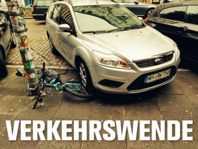 Parkendes Auto, dass mit dem linken Vorderrad auf dem Vorderrad eines abgestellten Mountainbikes steht. Darunter der Text: Verkehrswende