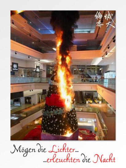 Ein riesiger brennender Tannenbaum in einem Einkaufszentrum in Hong Kong, darunter der Text: Mögen die Lichter erleuchten die Nacht