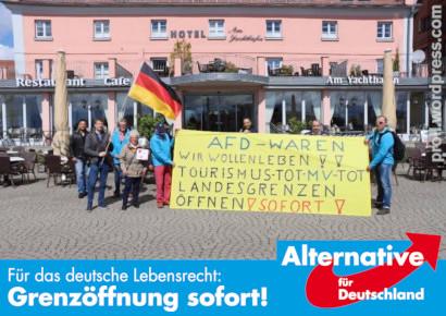 Foto einer Demonstration vor einem Hotel. Eine Gruppe mit einem Transparent: 'AFD-WAREN -- WIR WOLLEN LEBEN!! -- TOURISMUS TOT -- MV TOT -- LANDESGRENZEN ÖFFNEN! SOFORT! -- Dazu mein Text in Stil und Schriftarten der AfD-Wahlplakate: Für das deutsche Lebensrecht: Grenzöffnung sofort! Logo der Alternative für Deutschland
