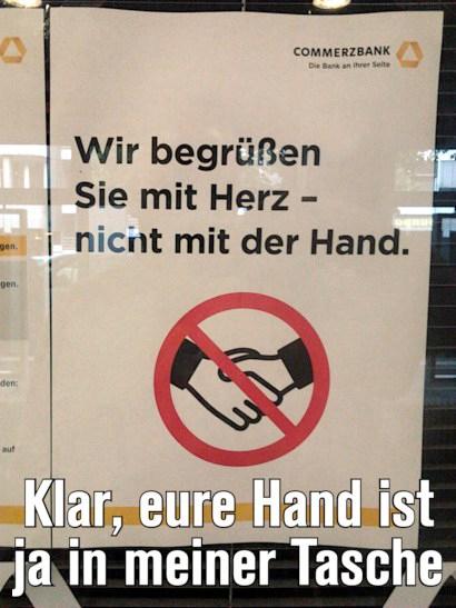 Aushang (zur Corona-Pandemie) in einer Commerzbank-Filiale: Wir begrüßen Sie mit Herz, nicht mit der Hand. Darunter mein Text: Klar, eure Hand ist ja in meiner Tasche