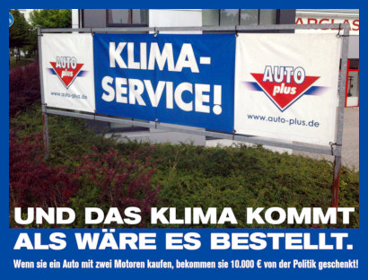 Foto einer Reklame im Straßenbild: KLIMASERVICE! AUTO plus www.auto-plus.de -- Dazu mein Text: Und das Klima kommt, als wäre es bestellt. Wenn sie ein Auto mit zwei Motoren kaufen, bekommen sie 10.000 € von der Politik geschenkt!