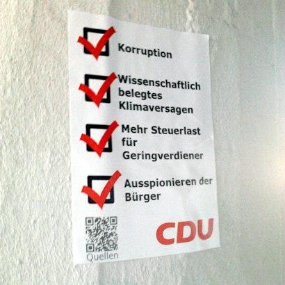 Aufkleber auf einem Betonpfeiler. Korruption (abgehakt), Wissenschaftlich belegtes Klimaversagen (abgehakt), Mehr Steuerlast für Geringverdiener (abgehakt), Ausspionieren der Bürger (abgehakt). QR-Code mit Link auf die Quellen. CDU